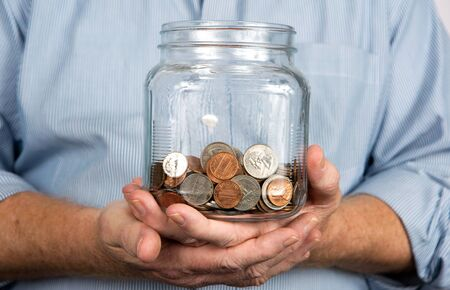 poor man: Man holds a glass jar containing United States coins and money. Stock Photo