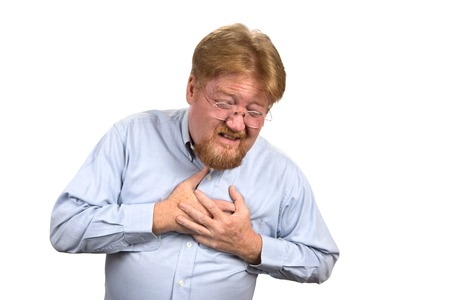 tightness: Mature man in his mid fifties clutches his chest as he reacts to heart attack pains.