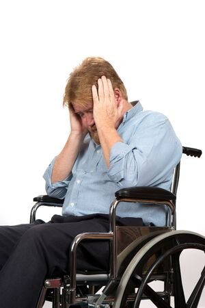 paraplegic: Elderly paraplegic in wheelchair holds his head in his hands as he suffers from depression because of a medical problem.