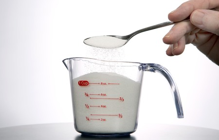 measure: Man pours a spoonful of sugar into a measuring cup. Stock Photo