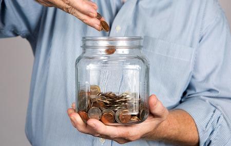 cuenta bancaria: Hombre cae dinero en un frasco de vidrio para una cuenta de ahorros.
