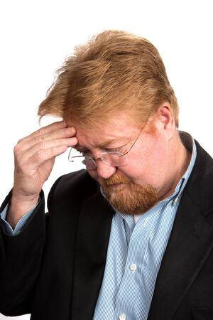 downcast: Worried and depressed mature businessman with red hair  holds his forehead in thought. Stock Photo