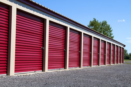 self storage: A row of mini rental units for temporary self storage in an outdoor setting. Stock Photo