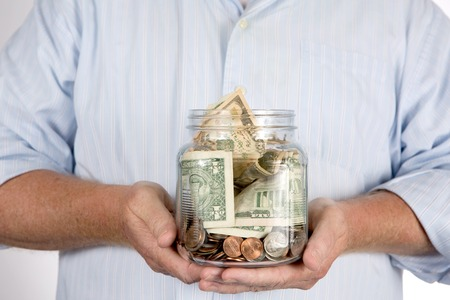 ira: Retired man holding his retirement piggy bank money account in his hands in a glass jar.