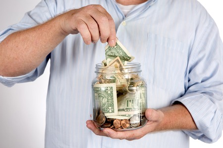 saving tips: Retiree withdraws money from his savings, bank, or IRA account piggy bank concept.