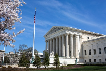 United States Supreme Court building and grounds with US Flag and cherry blossoms on tree. 報道画像
