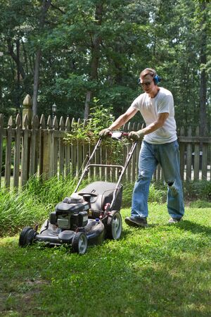ear protection: An elderly man wears ear protection to mute the loud noise of the lawn mower.