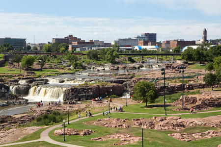 sioux: SIOUX FALLS, SOUTH DAKOTA, USA - AUGUST 8, 2015: Tourists visit Falls Park in Sioux Falls, South Dakota, USA with city skyline in the background on August 8, 2015.