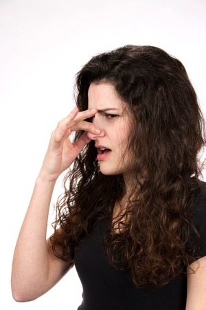 pinches: Woman pinches her nose in response to a stinky and smelly odor.