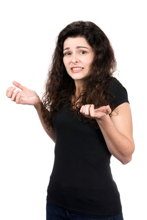 inability: Young woman shrugs her shoulders showing her indecision and inability to make a decision.