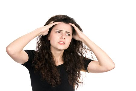worries: Anxious young businesswoman runs her fingers through her hair as she worries and stresses about her situation.