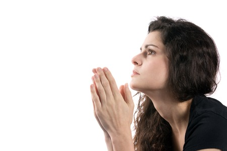 Woman prays while looking up with her hands together. Stock Photo