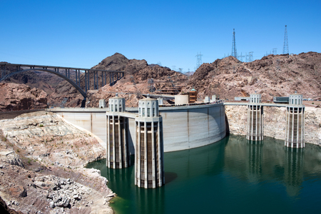 generates: Tourists walk along Hoover Dam located on the borders of Nevada and Arizona as generates electricity from the flow of the Colorado River, USA.