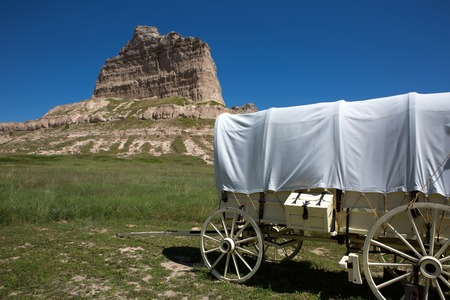 bluff: A covered wagon sits by Scotts Bluff National Monument depicting how settlers passed through the area on their migration west on the Oregon Trail in Nebraska.