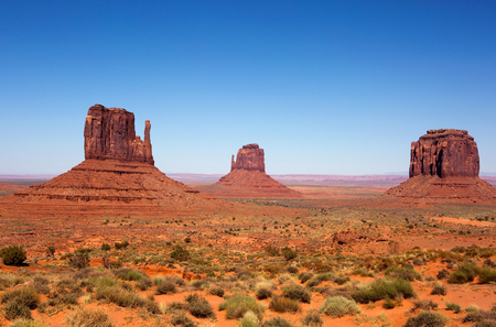 Three sandstone buttes in Monument Valley, Utah is part of the Navajo Tribal Park Reservation and is frequently used as a movie location in western desert scenes.