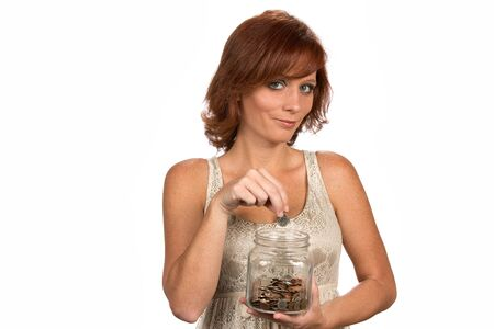 Smiling freckled redhead drops money into a clear glass savings jar as a financial banking concept.