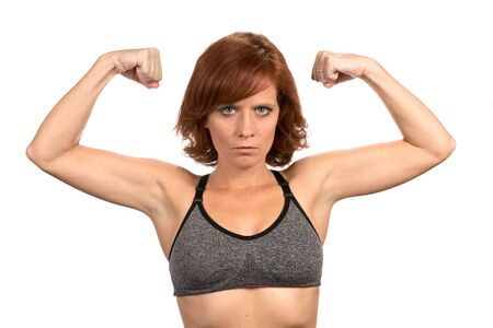 Thin freckled redheaded woman flexes her bicep muscles while wearing a sports bra.