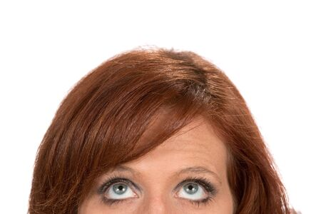 Top half of a redheaded woman as she looks up as a concept for thinking, thoughts and ideas.