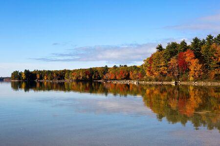 Autumn fall trees reflect colors on Lake Sabago, Maine, USA.
