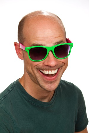 Man with a silly grin on his face wears colorful sunglasses.