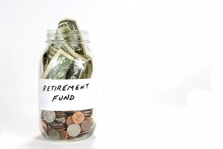 Clear glass jar holds money for retirement fund.