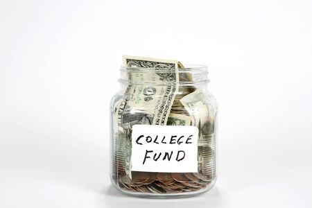 Glass jar filled with coins and paper money with a label written college fund.