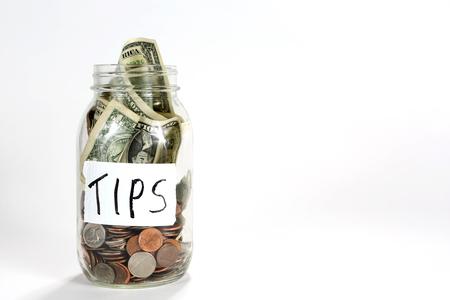 Il vaso di conservazione di vetro con le monete e le fatture del dollaro hanno un'etichetta con le punte scritte su esso. Archivio Fotografico - 72184256