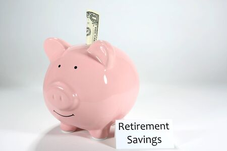 One dollar sticks partly in a pink piggy bank with a label stating retirement savings.