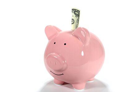 Pink piggy bank has one USA dollar sticking out of slot. Reklamní fotografie