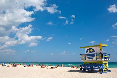 MIAMI BEACH, FLORIDA - FEBRUARY 15, 2017: Tourists sunbath on Miami Beach, Florida, USA, next to a colorfully painted lifeguard station on February 15, 2017. Redakční