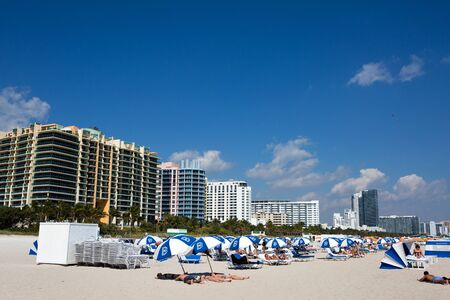 MIAMI BEACH, FLORIDA - FEBRUARY 15, 2017: Vacationers sunbath on Miami Beach, Florida, USA, with hotels and condominiums in the background on February 15, 2017. Редакционное