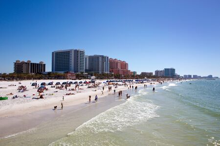 Tourists swim and play at the beach on Clearwater Beach, Florida with luxury hotels in the background.