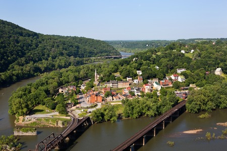 Aerial view of the town of Harpers Ferry, West Virginia, which includes Harpers Ferry National Historical Park, located between the Potomac River and the Shenandoah River. Traffic can be seen moving along the bridge in the distance.