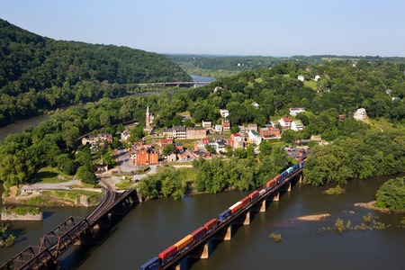 A train rolls across the Shenandoah River in an aerial view of the town of Harpers Ferry, West Virginia, which includes Harpers Ferry National Historical Park, located between the Potomac River and the Shenandoah River. Redakční