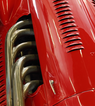 bodywork: Closeup of the exhaust and bodywork of a red classic racing car  Stock Photo