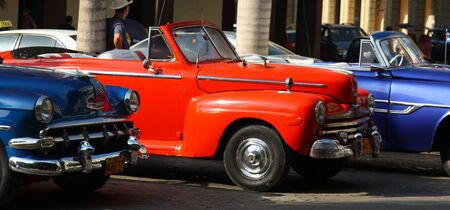 habana: A line of red and blue classic America cars in a street in Havana, the capital of Cuba  Editorial