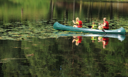 A mother, father, and child in a canoe on a reflective lake in a wooded park. photo