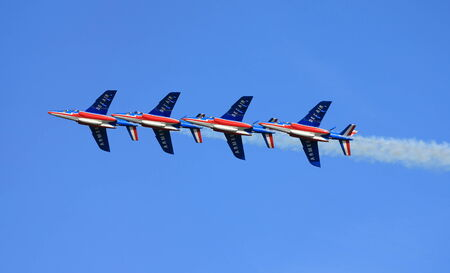 astern: The French Patrouille de France aerobatic group fly in line astern formation during a public airshow.