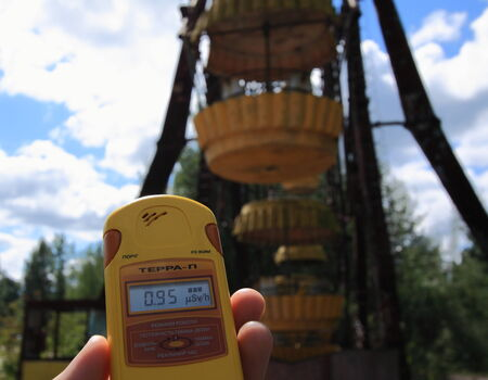pripyat: Tourist with a dosimeter takes a radiation reading in the fairground in the abandoned town of Pripyat, Ukraine. The town was abandoned after the 1986 Chernobyl nuclear disaster and is now in the zone of alienation, visited by a few adventurous tourists.
