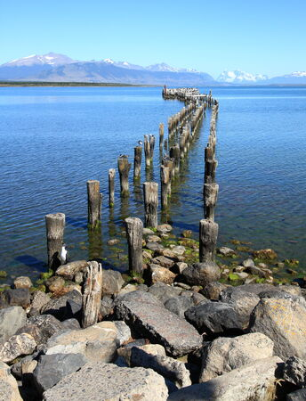 puerto natales: Wooden pier and a smooth, calm ocean viewed from Puerto Natales, Patagonia, Chile.