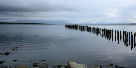 Wooden pier and a smooth, calm ocean viewed from Puerto Natales, Patagonia, Chile. photo