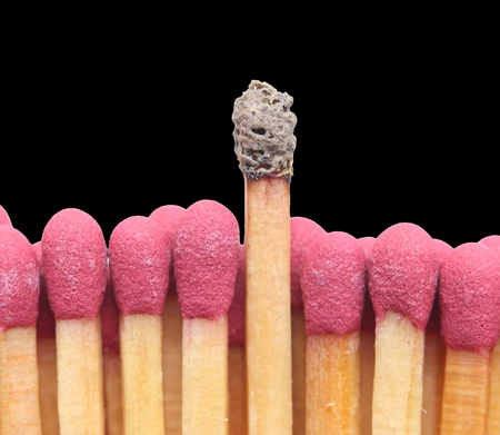 standing out: Group of matches with one burnt match standing out above the others. Isolated on black background.