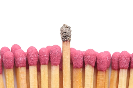 burnt out: Group of matches with one burnt match standing out above the others. Isolated on white background.
