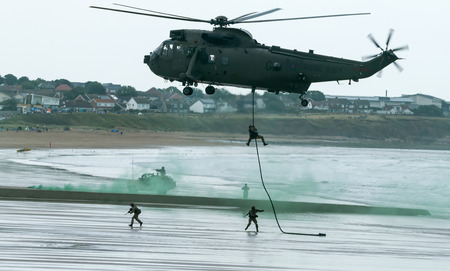 public demonstration: British Royal Marine Commandos fast-line from a helicopter perform a beach assault demonstration for the public at the 2015 Sunderland Airshow.