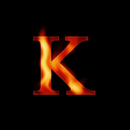 fire letter K isolated on dark background photo