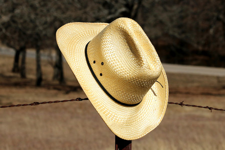 Close-up of a yellow straw cowboy hat hanging on a barbed wire fence post.