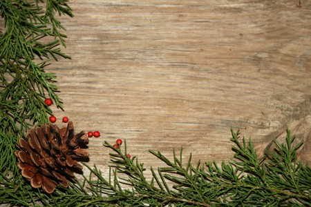 Cedar Branches and a pine cone frame a wood grain background with room for text.