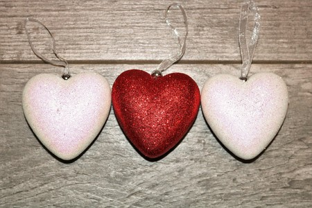 Two white and one red glitter hearts on a wood grain background. Room for text on hearts.