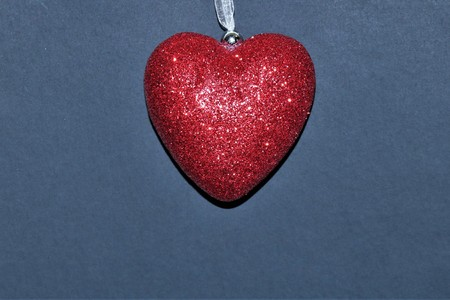 A large red glitter heart isolated on a dark blue background.