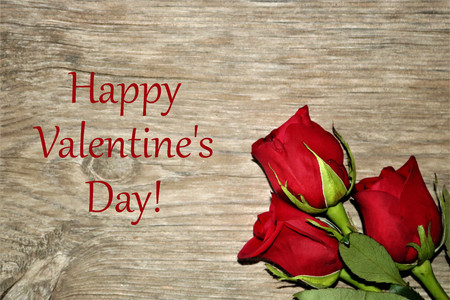 Happy Valentine's Day text on a wood grain background with three red rose buds in lower right corner. Stock Photo
